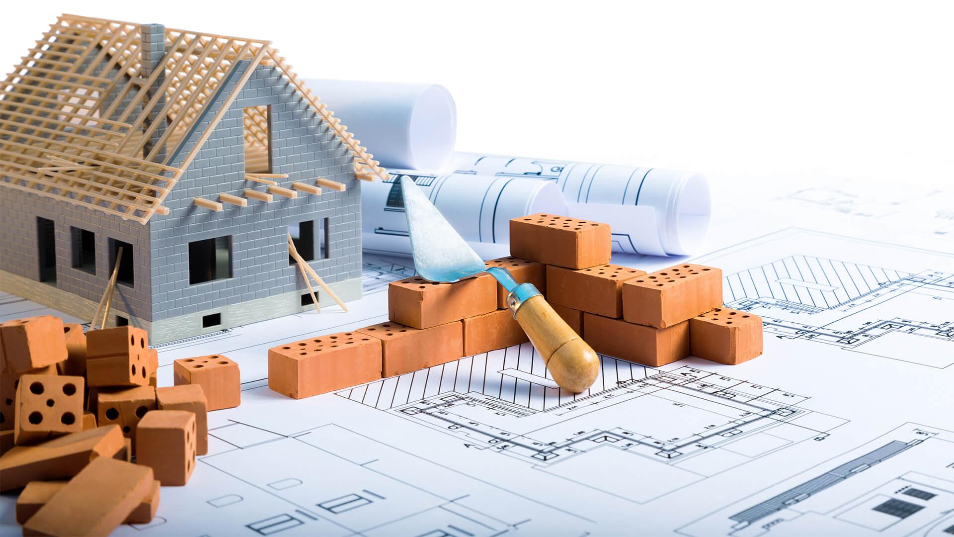 model house on blueprints, with miniature bricks