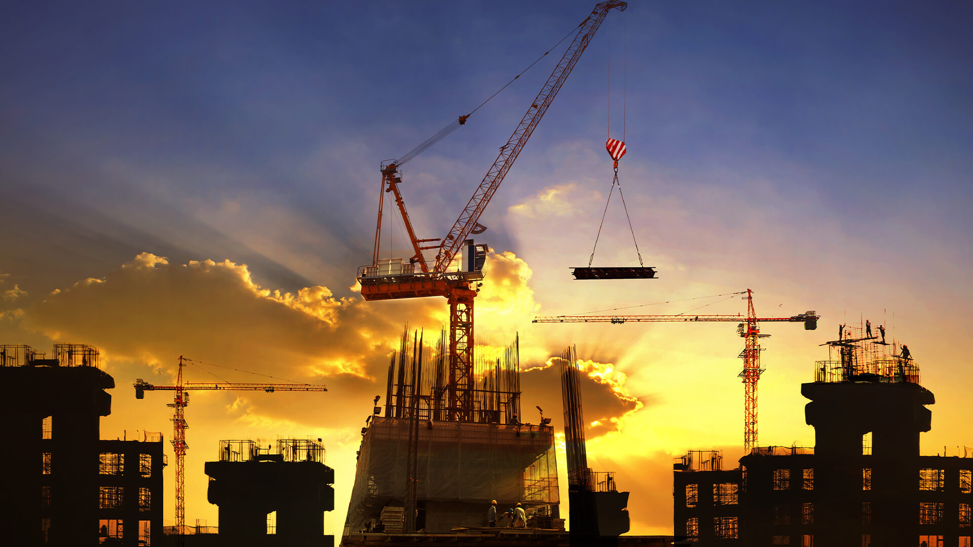silhouette of high rise construction against a sunset