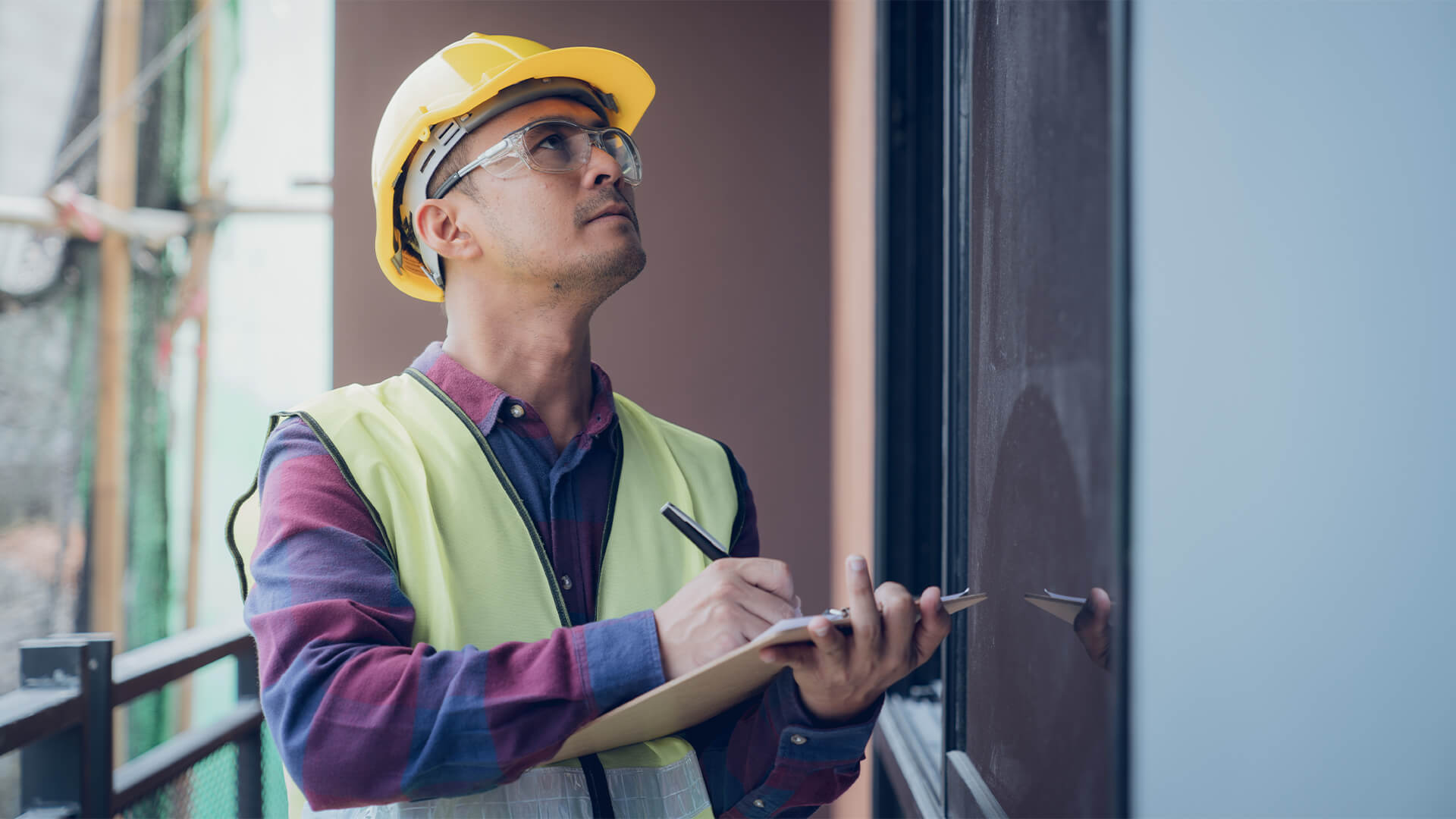 Foreman on a build site inspecting a window