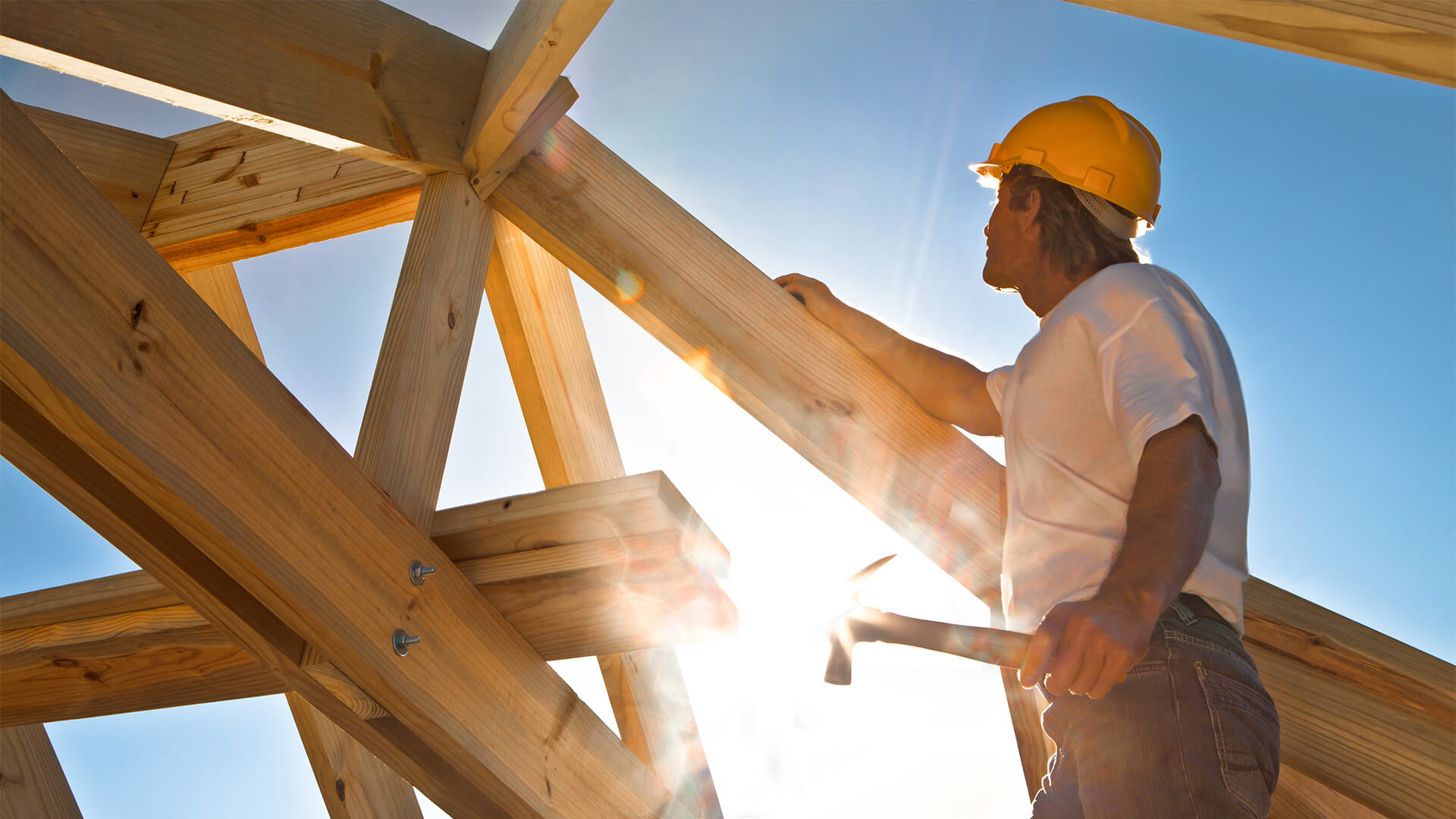 Man working in construction, hammering a wooden house frame in place with the sun in the background