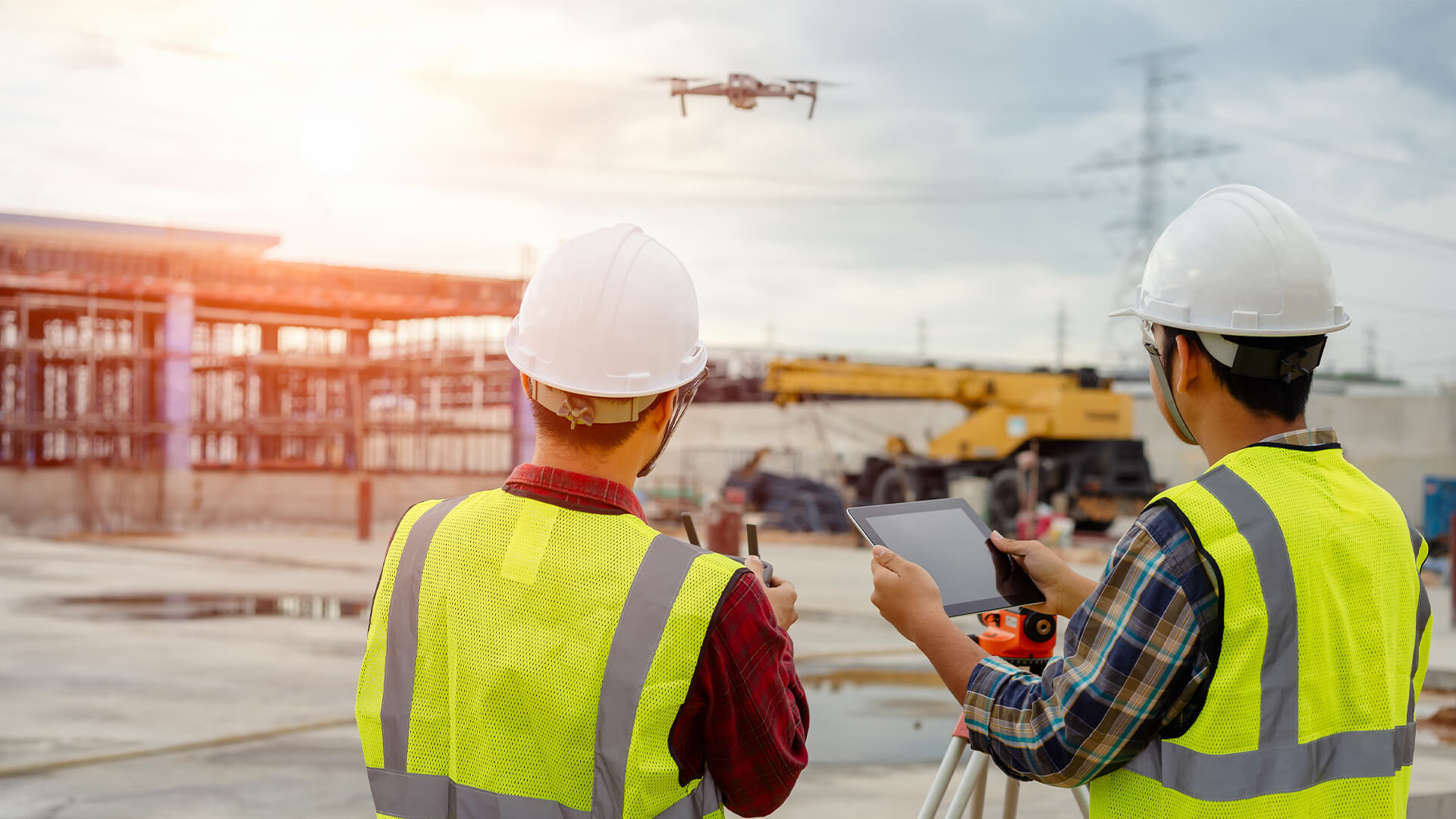 Two construction workers on site with a drone and tablet to map out the area