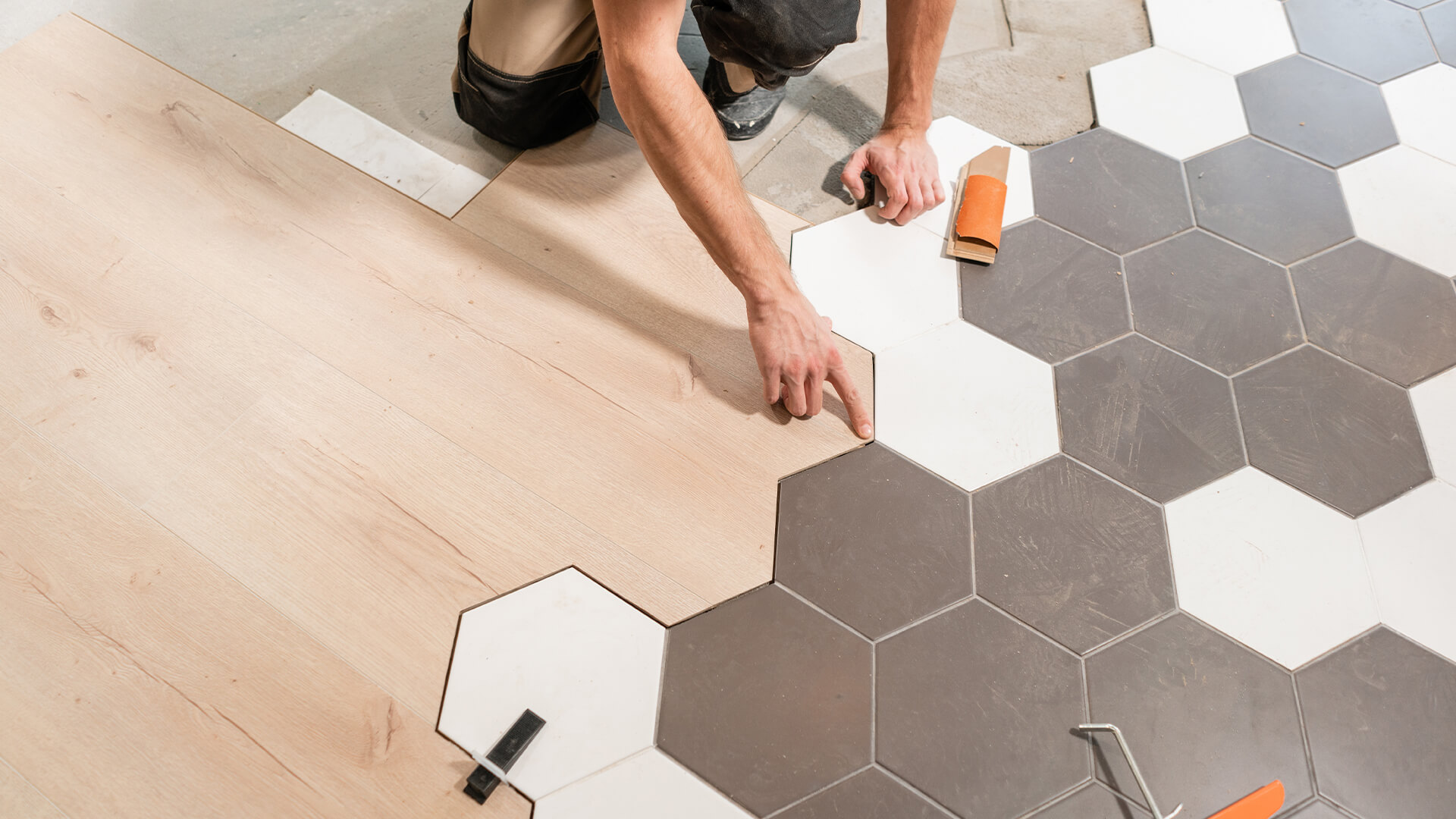 A man laying hexagonal tiles in his home