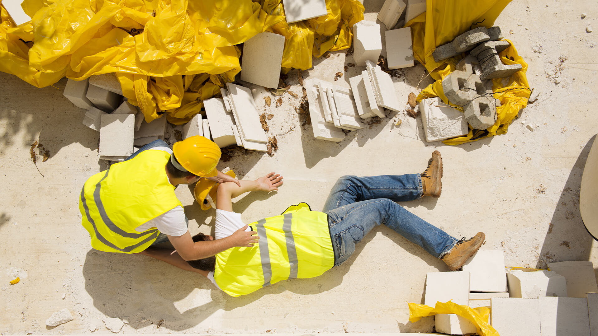 First aid construction worker helping an injured colleague