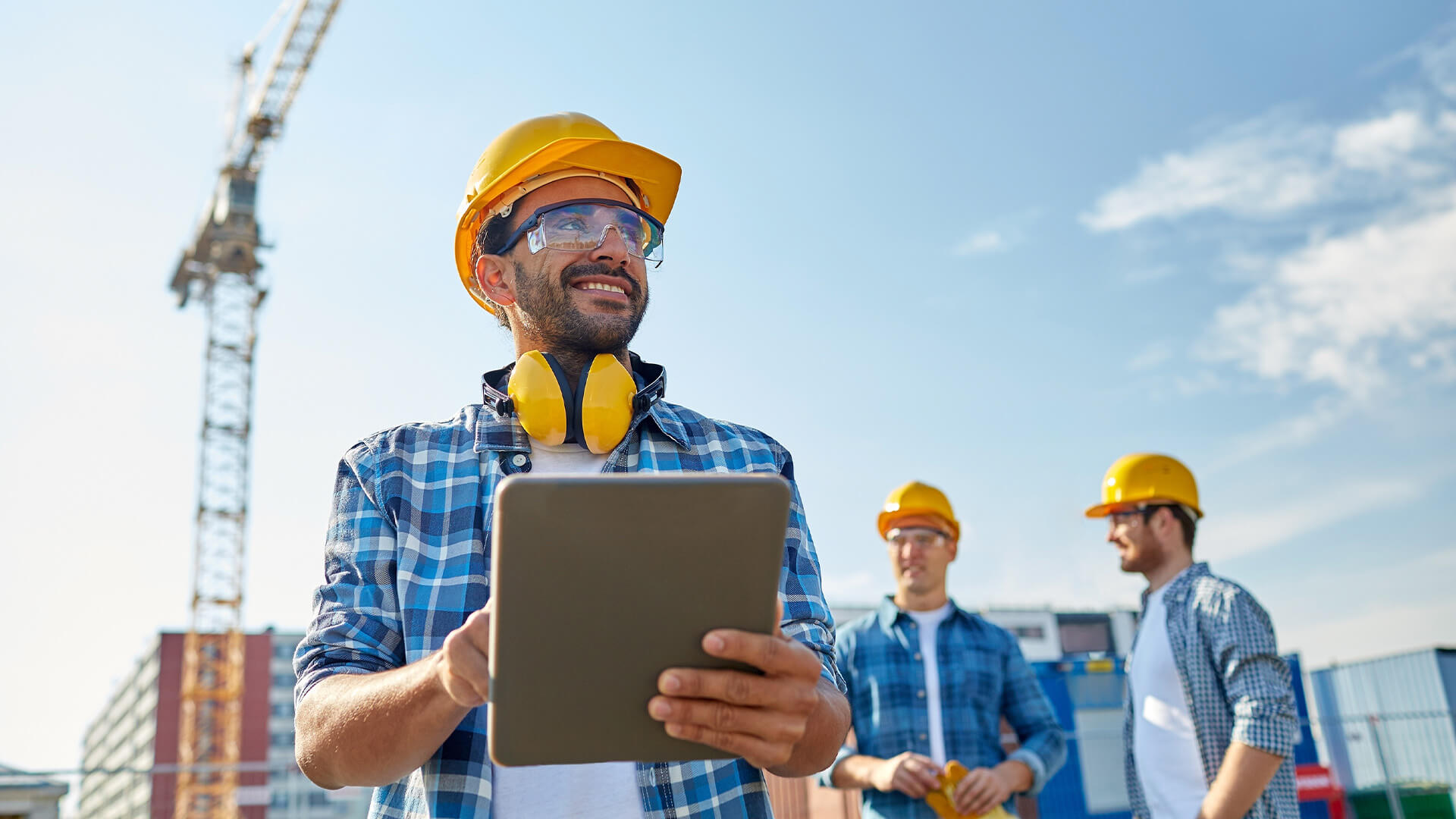 Mananger of a construction site with protective gear and a tablet, smiling
