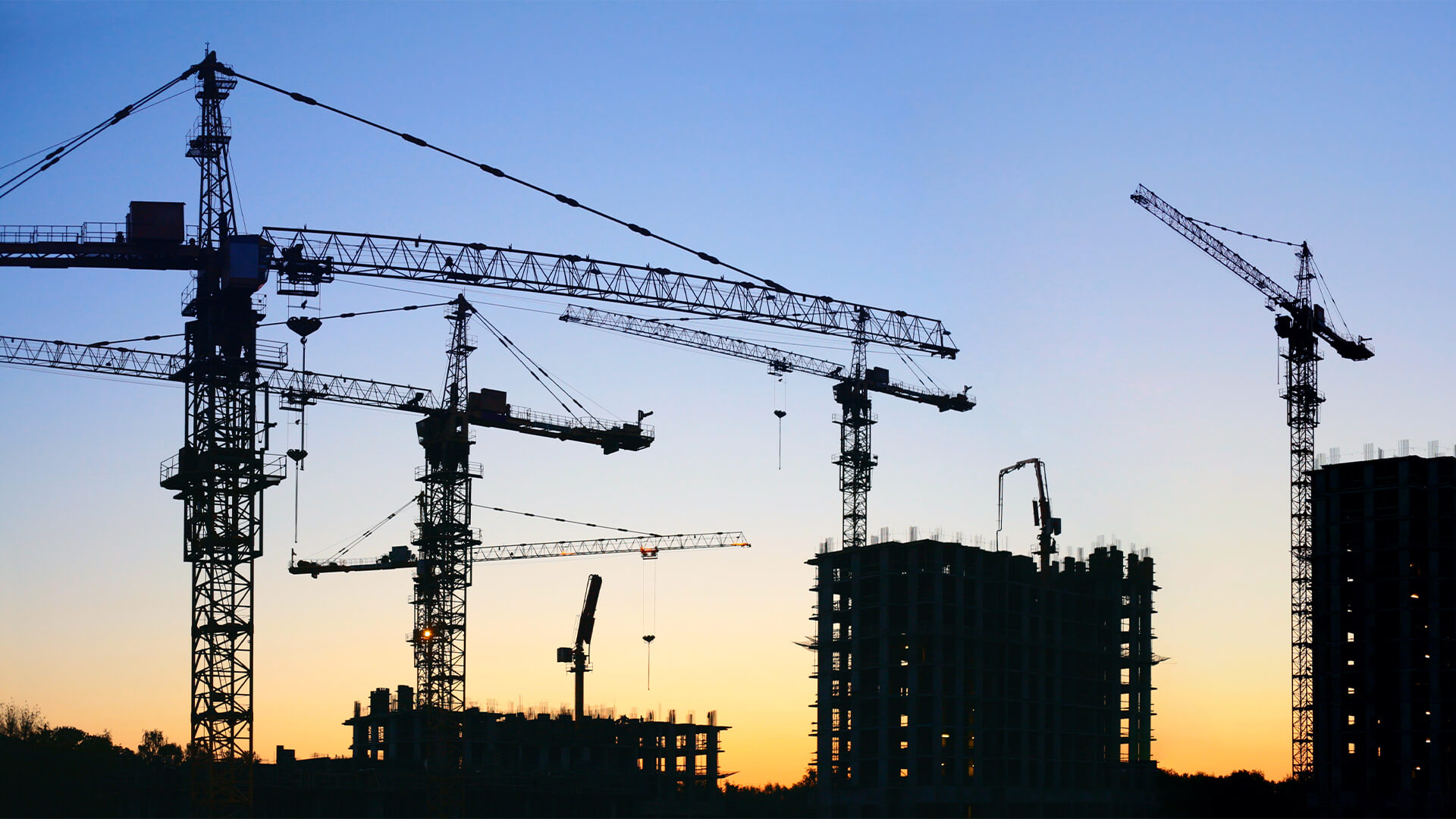 Silhouette of cranes on a construction site against a sunset