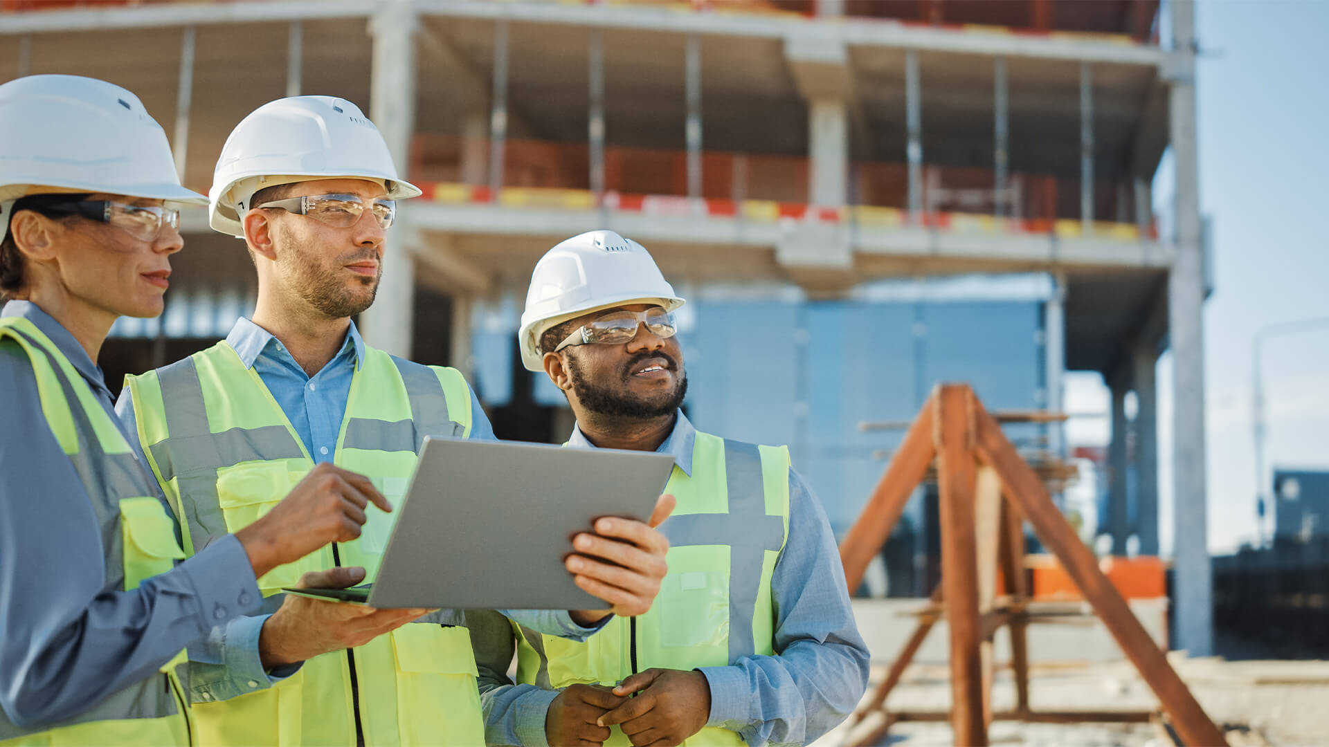 Three workers at a construction site with a tablet, checking the plans