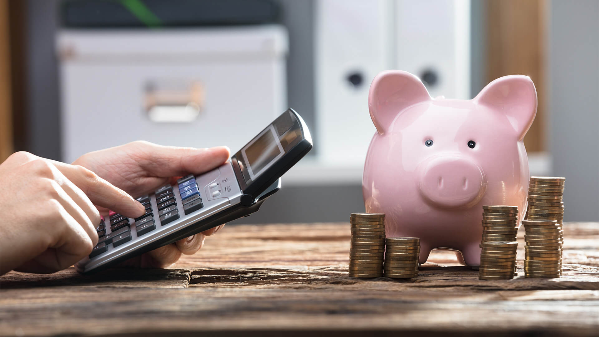 Man making a budget with a calculator and a piggy bank