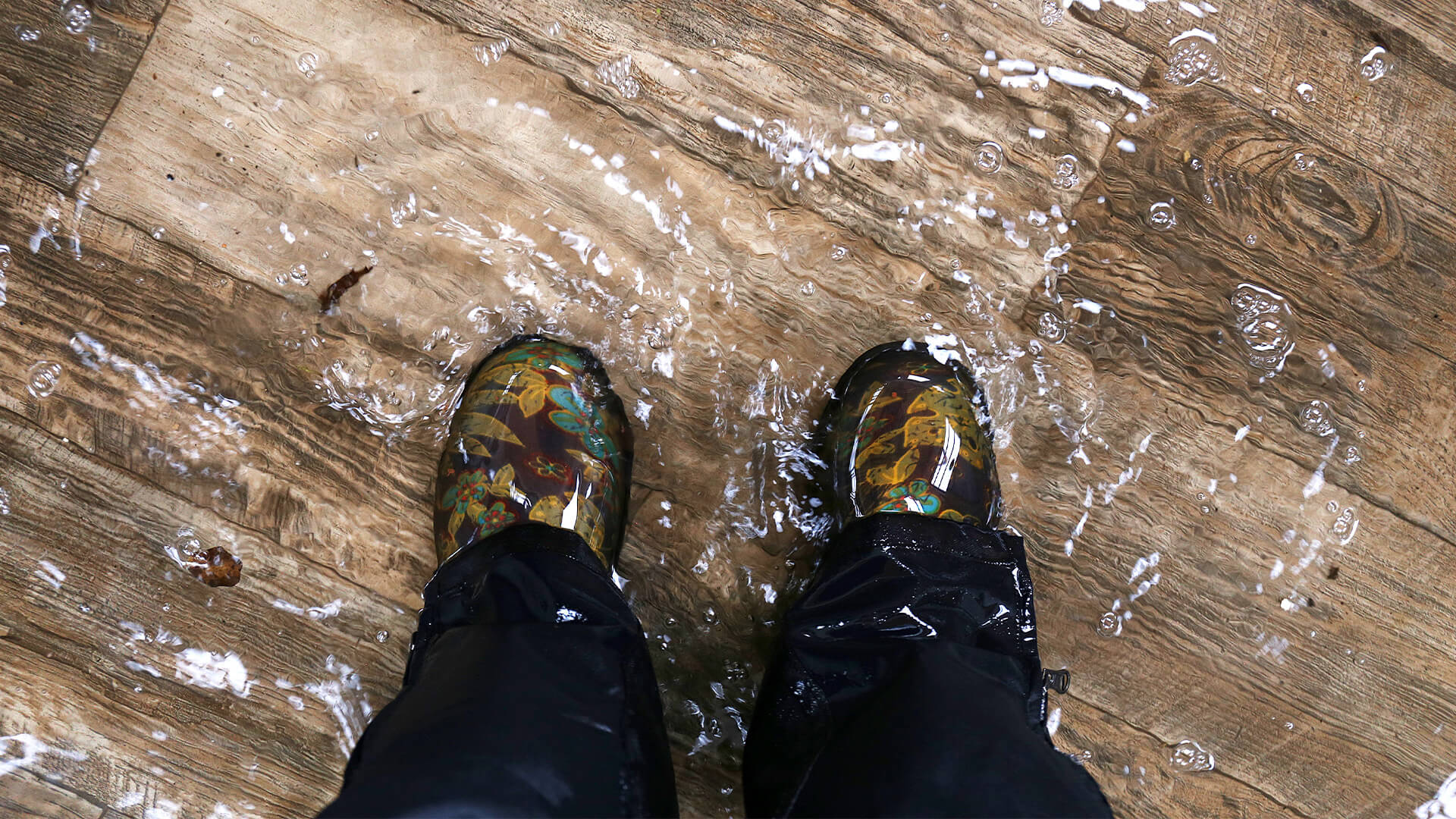 Perspective image with the camera looking at feet on a flooded wooden floor