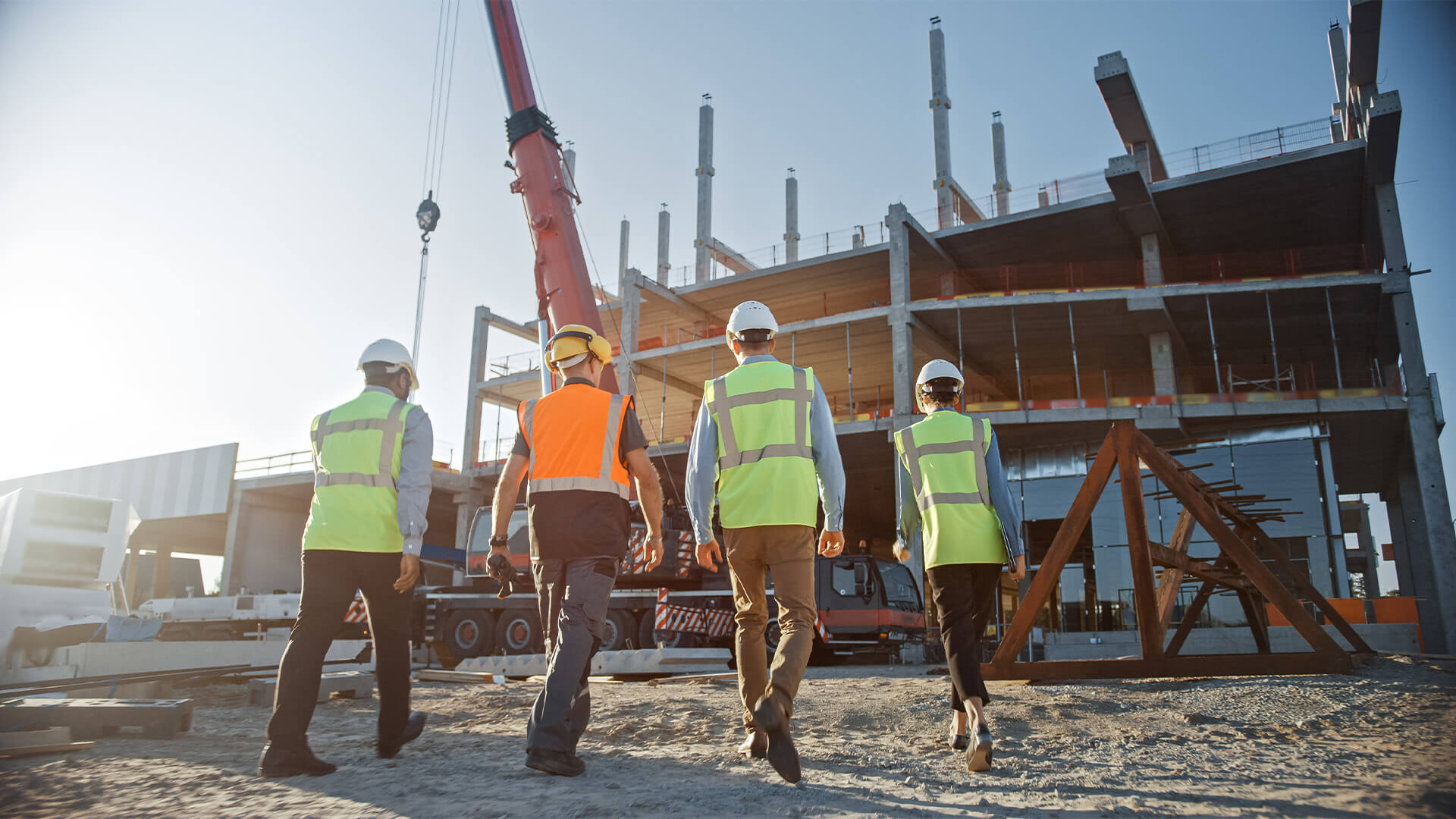 Four people in safety gear walking through a construction site
