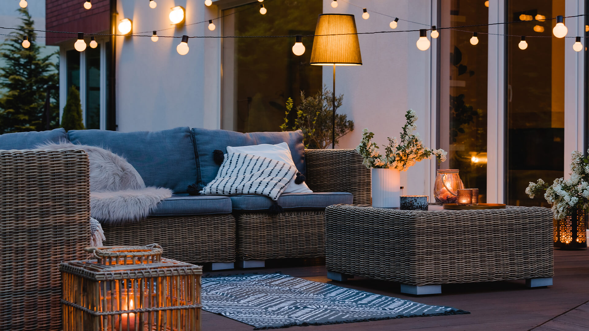 Outdoor sitting area of a rented home. There are comfy chairs, an outdoor rug, and fairy lights